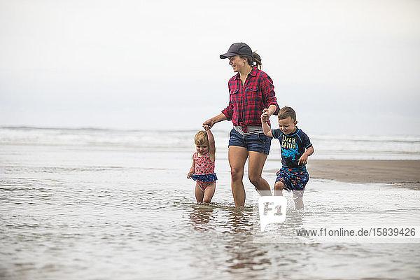 Mutter watet mit ihren beiden Kindern in den Ozean.