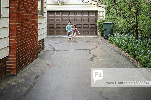 A small boy and girl play basketball together in driveway  barefoot