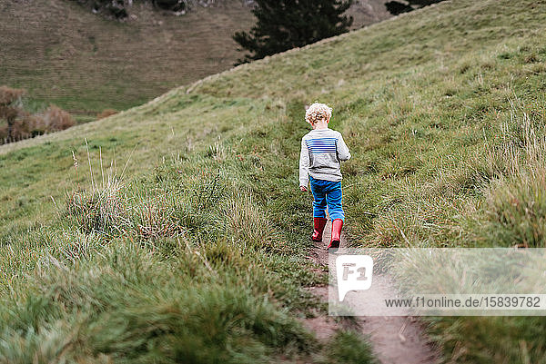 Kleiner Junge mit lockigem Haar  der auf einem Bergweg geht