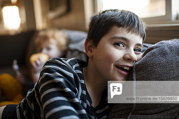 Happy 7-8 year old boy laying on couch smiling at home