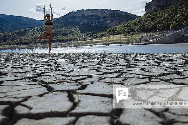 Frau  die auf einem Bein am Rand eines Sees balanciert.