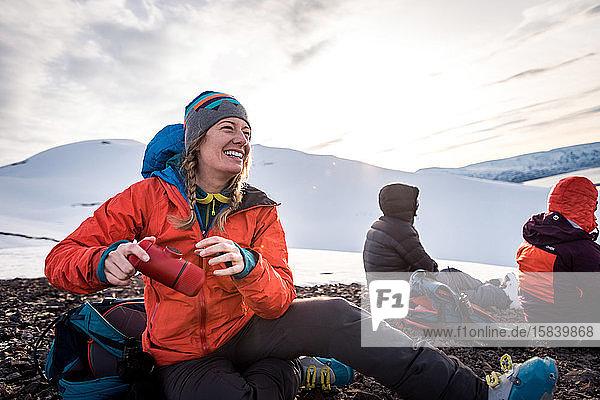 Frau lacht mit Kaffeemaschine  während draußen im isländischen Schnee