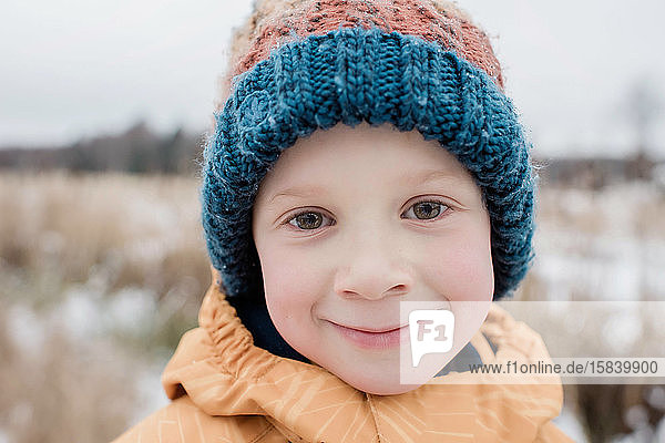 portrait of a young boy smiling whilst playing outside in winter