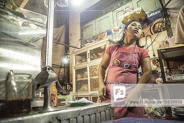 Thailänderin  die auf einem Straßenlebensmittelmarkt arbeitet