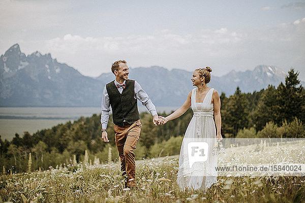 glückliche Braut und Bräutigam gehen durchs Feld vor den Bergen Wyoming