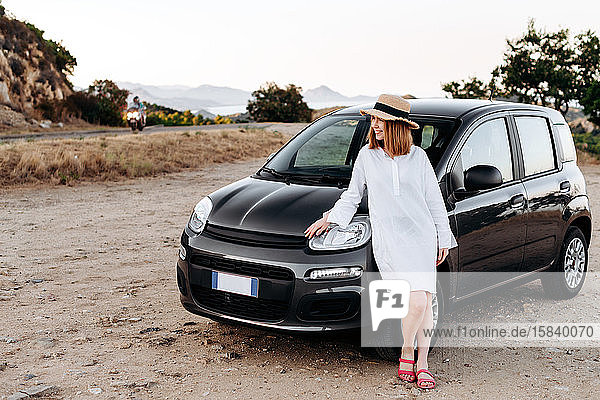 Ein süßes  charmantes Mädchen mit Strohhut posiert um ein schwarzes Auto am Straßenrand.
