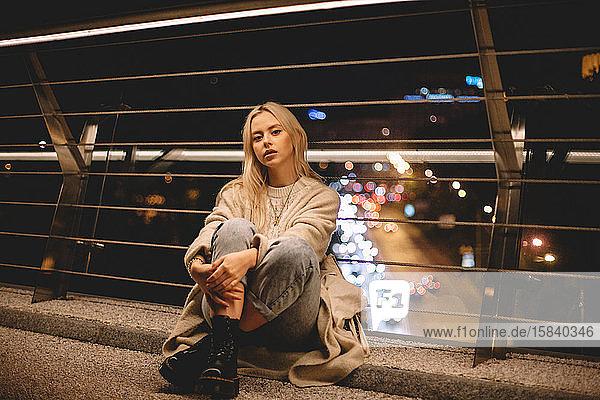 Porträt einer jungen Frau  die nachts auf einer Brücke in der Stadt sitzt