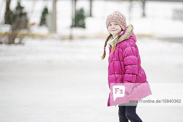 Kleine Mädchen laufen Schlittschuh im Freien