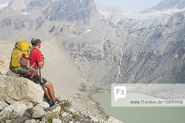 Wanderer sitzt auf einem Felsen mit Blick auf den Wasserfall.