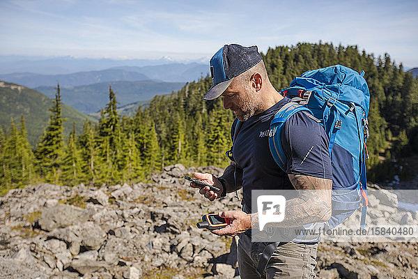 Wanderer paart sein Telefon und GPS  um im Hinterland zu navigieren.