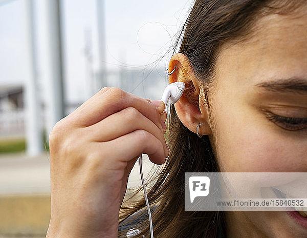 Frau setzt sich ein weißes Headset ans Ohr.