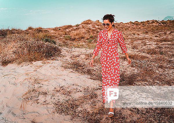 Schöne Frau in rotem Kleid bei Sonnenuntergang in die weißen Sanddünen
