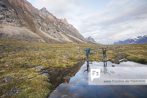 Reflexion von Wanderern  die am Akshayak-Pass Stöcke hochhalten