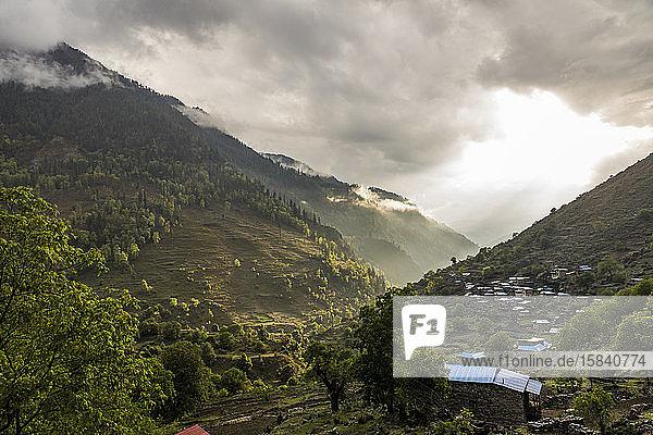 Landschaft mit grünem Bergtal und Dorf bei Sonnenuntergang in Nepal