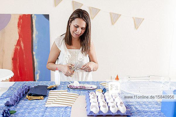 Lächelnde Frau schneidet mit goldener Schere im Atelier am Kunsttisch