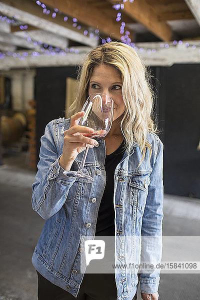 Junge attraktive Frau  die an einem Glas Rotwein auf einem örtlichen Weingut riecht.