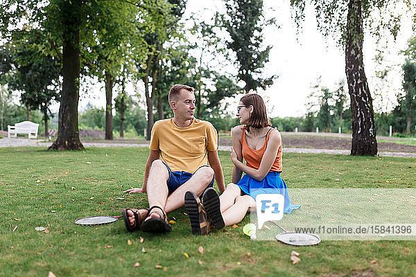Tausendjähriges Ehepaar sitzt im Gras  nachdem es im Park Badminton gespielt hat