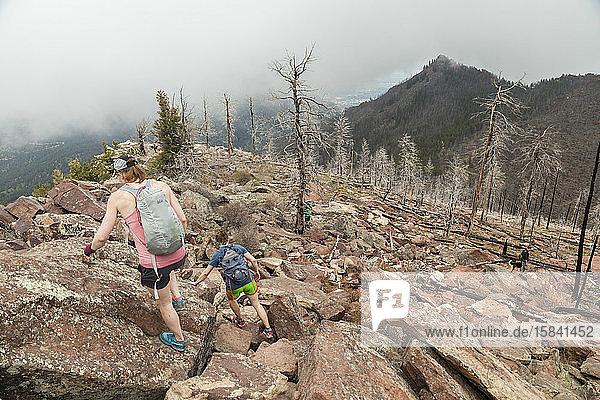 Frauen wandern den South Boulder Peak  Colorado  in der Nähe verbrannter Bäume hinunter