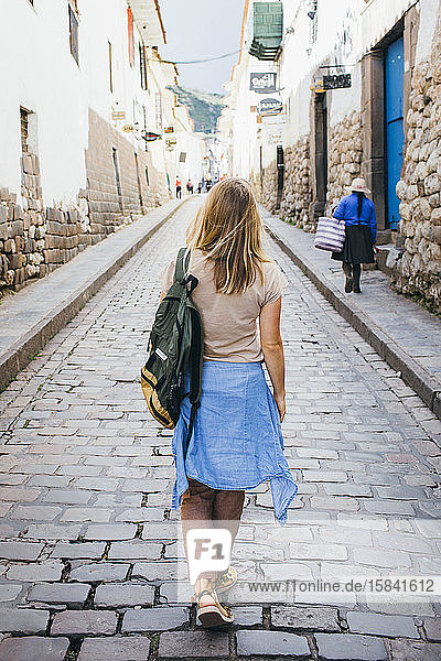 A young woman is walking down the street of the city of Cusco  Peru