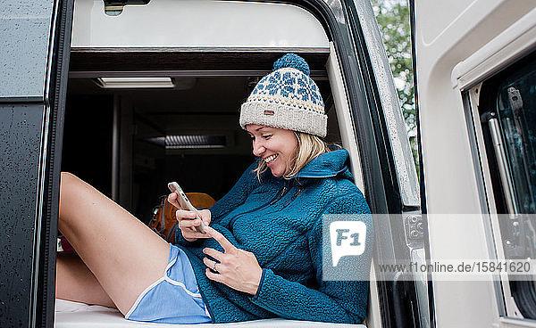 Porträt einer Frau  die beim Camping über ihr Handy lacht