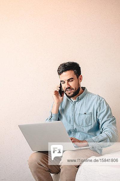Mann spricht mit einem Smartphone  während er zu Hause einen Laptop benutzt