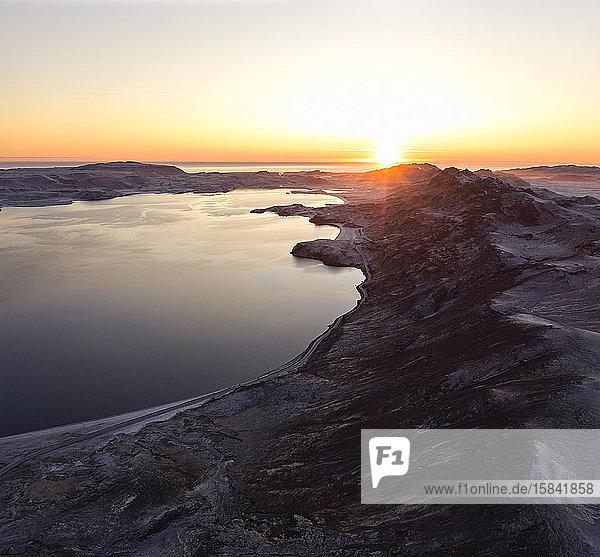 Wunderschöner Sonnenuntergang über steinigem Ufer