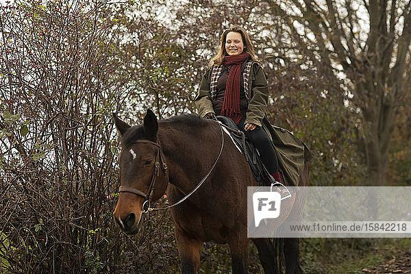 junge Reiterin mit einem Pferd beim Ausritt