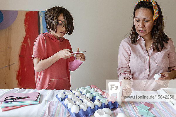 Boy taking photo while mom craft confetti egg project
