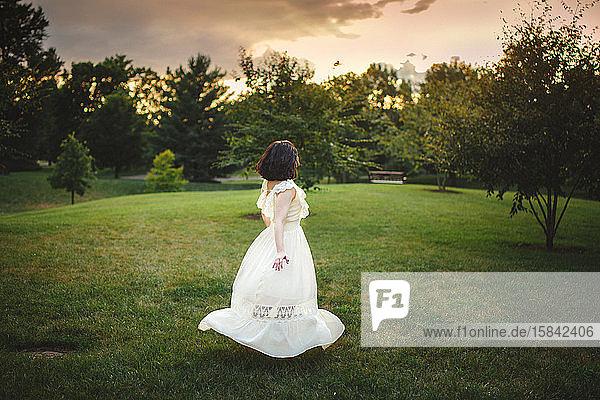 Eine Frau geht in einem langen weißen Kleid bei Sonnenuntergang durch einen von Bäumen gesäumten Park