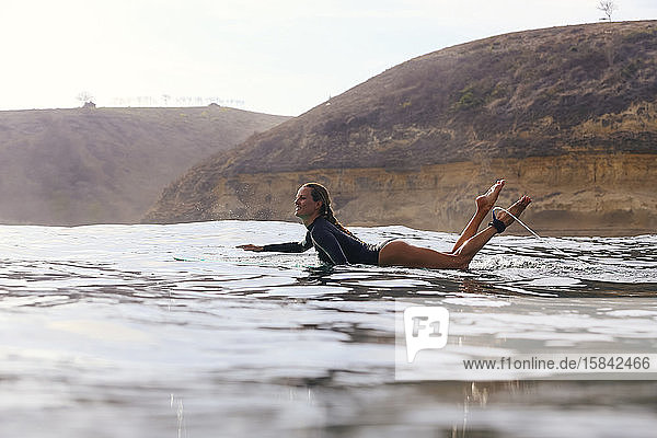 Glückliche Frau sitzt auf einem Surfbrett im Meer