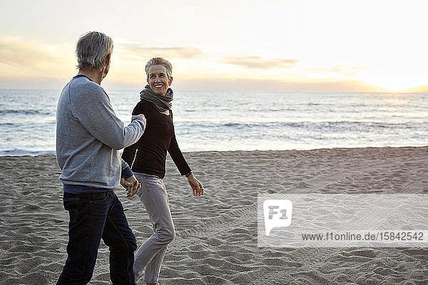 Lächelndes älteres Paar hält sich beim Strandspaziergang bei Sonnenuntergang an den Händen