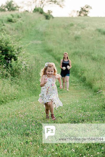 Eine Mutter und ihre Mädchen gehen über eine Wiese und pflücken Wildblumen.
