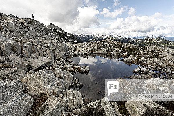 Ein Mann nimmt den Blick auf die Berge ein  in denen er wandert.