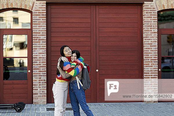 Beste Freunde junger Studenten umarmen sich vor dem roten Gebäude