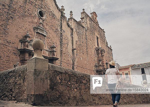 Touristisches Mädchen geht vor einer alten Steinkirche in einem Dorf in Spanien