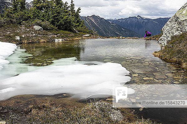 Eine Frau kauert sich an einem Sommertag in den Bergen von Britisch-Kolumbien hin und spürt das Wasser am Rand eines alpinen Pools.