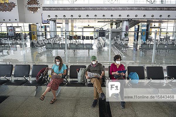 Dreiköpfige Familie  die aufgrund der globalen Gesundheitskrise durch das Coronavirus Gesichtsmasken trug  während sie auf einem verlassenen Flughafen in Khajuraho  Madhya Pradesh  Indien  wartete.