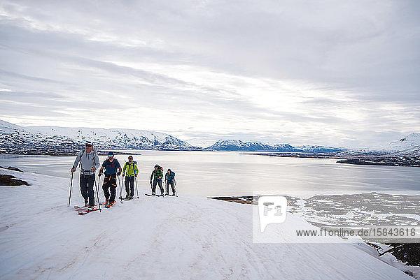 Eine Gruppe beim Skilanglauf in Island mit dem Ozean im Hintergrund