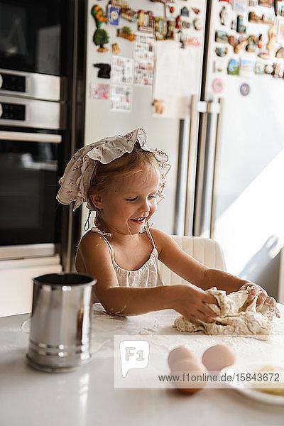 Kleines Mädchen kocht Pizza in der Küche