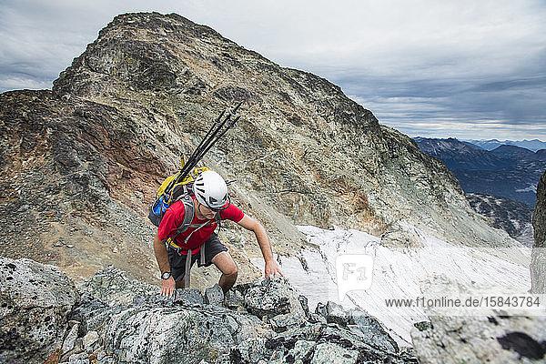 Hochwinkelaufnahme eines Rucksacktouristen  der einen felsigen Berg besteigt.