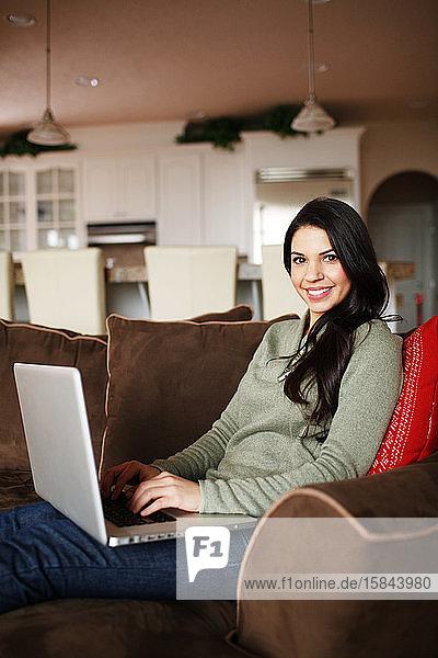 Frau am Laptop in ihrem Wohnzimmer  die in die Kamera schaut