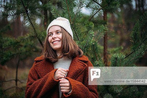 Hübsche Frau in warmer Kleidung steht an Kiefern im Wald