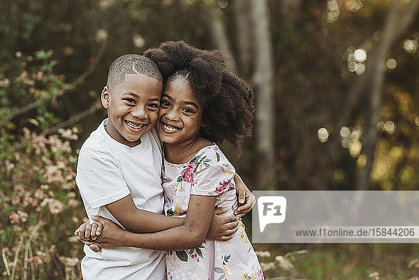 Close up portrait of brother and sister smiling at camera