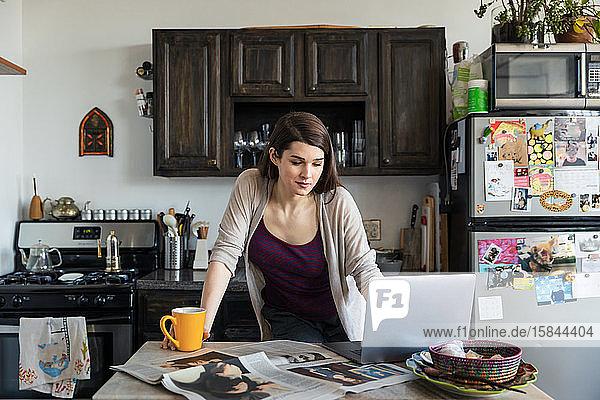 Junge Frau benutzt Laptop  während sie in der Küche Kaffee am Tisch trinkt