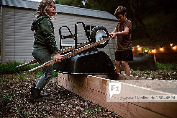 Geschwister arbeiten gemeinsam auf einem Hochbeet mit Erde aus der Schubkarre