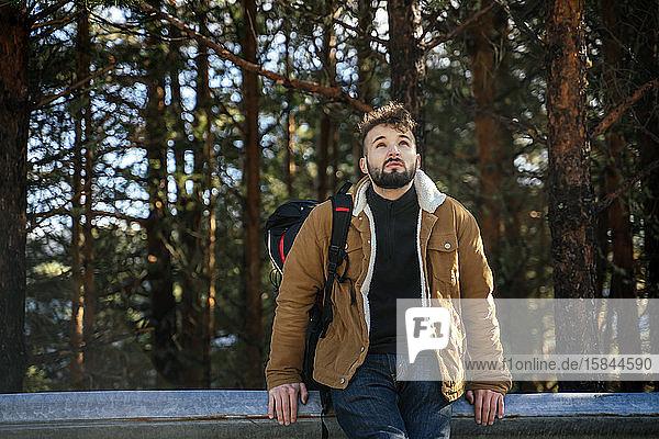 Tourist auf dem Berg  der auf der Leitplanke sitzt
