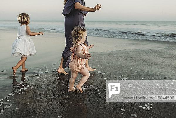 Hinteransicht einer jungen Familie,  die bei Sonnenuntergang auf das Meer zugeht