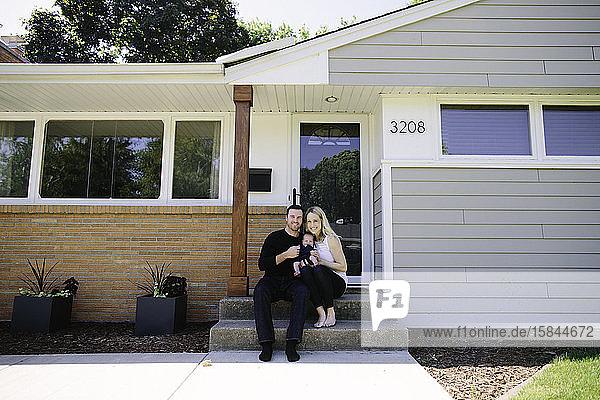 Neue Eltern sitzen mit ihrem Neugeborenen auf der Vordertreppe ihres Hauses