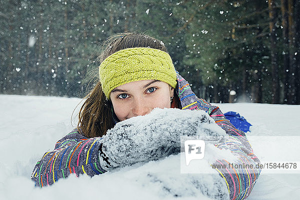 das Mädchen liegt im Schnee und lächelt