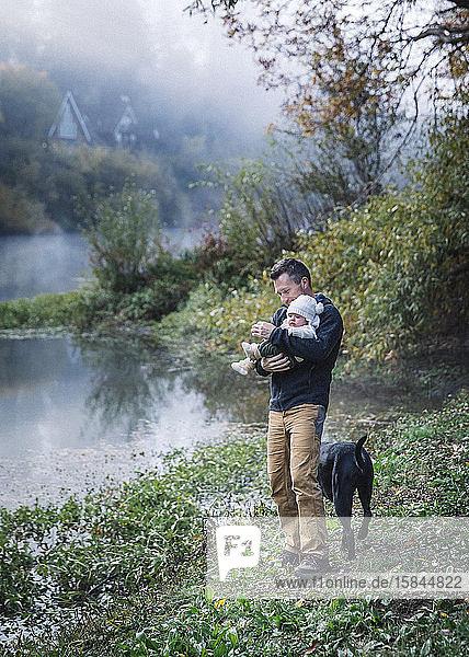 Ein Mann hält ein Baby in der Nähe eines Flusses und einen Hund